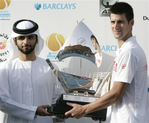 Novak Djokovic wins in Dubai and receives trophy from Sheik Monsoor bin Mohammed.