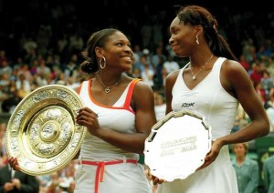 Venus accepts the runner up trophy while Serena wins the Wimbledon Championship Trophy in 2003