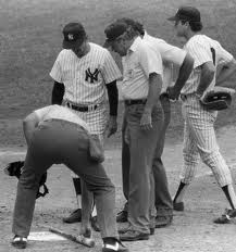 "Billy Martin observes as umpire Tim McClelland inspects the ""pine tar"" bat."